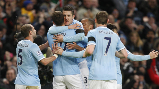 Manchester City's Stevan Jovetic, facing, celebrates after scoring the opening goal with teammates during the English FA Cup fifth round soccer match against Chelsea at the Etihad Stadium, Manchester, England, Saturday, Feb. 15, 2014. (AP Photo/Jon Super)