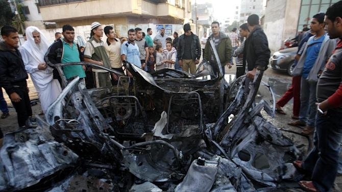Palestinians look at the wreckage of a car after an Israeli air strike that killed several people in Gaza City,Tuesday, Nov. 20, 2012.(AP Photo/Hatem Moussa)