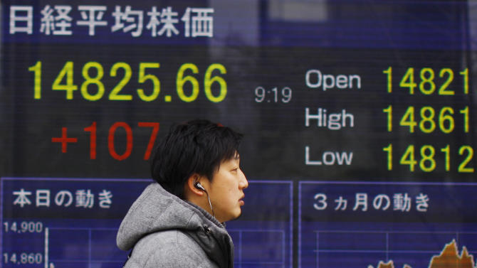 A man walks outside a securities firm in Tokyo, Wednesday, Feb. 12, 2014. Tokyo stocks jumped in early trading Wednesday, a day after a surge on Wall Street that followed reassurance from the new head of the U.S. Federal Reserve about continued low-interest rate policies. (AP Photo/Junji kurokawa)
