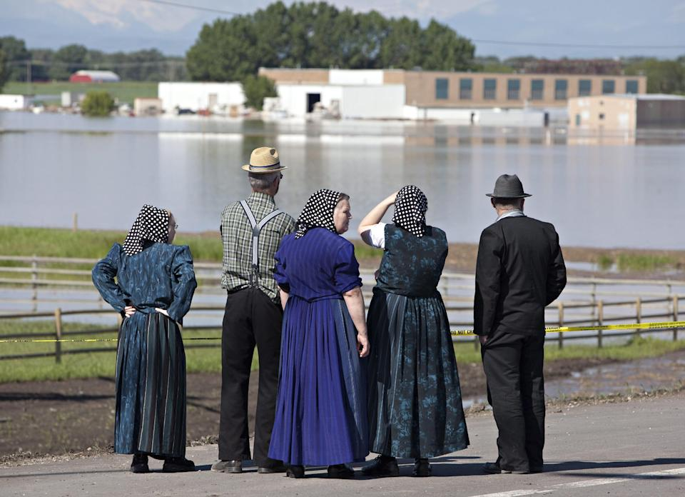 Hutterites from the Parkland Colony survey the flood zone in High River, Alberta, Canada on Saturday, June 22, 2013 after the Highwood River overflowed its banks. (AP Photo/The Canadian Press, Jordan Verlage)
