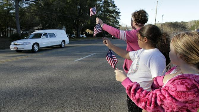 """Gabriel Cavender, right, Kiya Buchanan, center, and Raechel Buchanan, left, hold up flags as the funeral procession for Charles """"Chuck"""" Poland passes by on Sunday, Feb. 3, 2013, in Ozark, Ala. (AP Photo/Butch Dill)"""