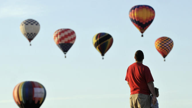 """Matt Brenner and his son Grey, 3, of Rio Rancho, watch mass ascension just north of Balloon Fiesta Park, on the first morning of the Albuquerque International Balloon Fiesta, Saturday, Oct. 2, 2010, in Albuquerque, N.M. """"There's lots of balloons,"""" Grey said. (AP Photo/Albuquerque Journal, Marla Brose) **EXAMINER ONLINE OUT**"""