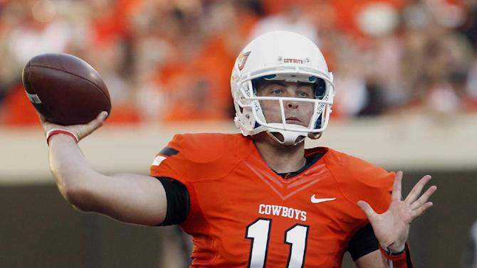 In this Sept. 1, 2012 file photo, Oklahoma State quarterback Wes Lunt throws against Savannah State during an NCAA college football game in Stillwater, Okla. Illinois head coach Tim Beckman says he's in no hurry to name a starting quarterback and that the competition between the three potential candidates to succeed Nathan Scheelhaase is wide open. Lunt brings a skill set and a pedigree that the Illini haven't seen in a while. The tall, strong-armed quarterback sat out last season after transferring from Oklahoma State