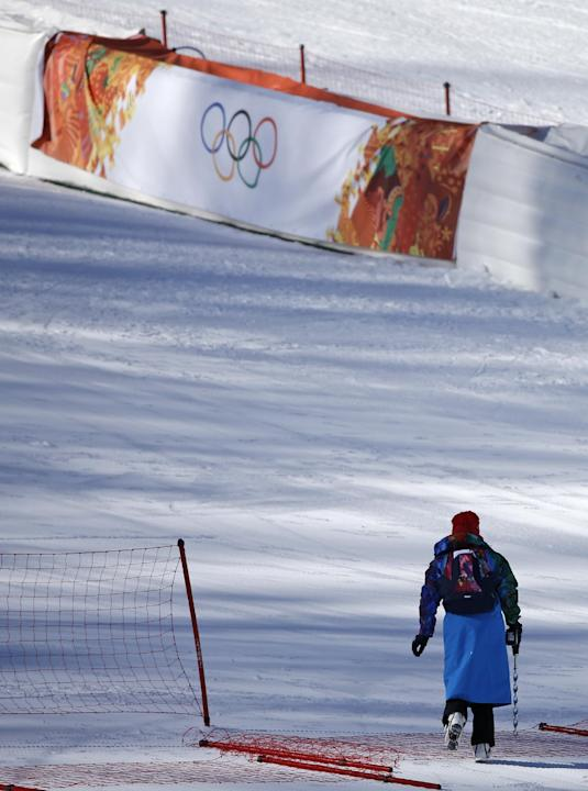 A worker carries a drill used to secure the poles that hold the safety fencing in the finish area of the alpine skiing at the Sochi 2014 Winter Olympics, Wednesday, Feb. 5, 2014, in Krasnaya Polyana,