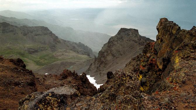 This Aug. 4, 1999 file photo shows a rocky outcrop on Steens Mountain in southeastern Oregon. Dustin Self, 14, of Piedmont, Okla. was missing on the mountain, where a rancher found his abandoned pickup truck on Tuesday, April 18, 2013. The 30-mile long fault block of basalt is the highest point in the desert of southeastern Oregon at 9,773 feet. (AP Photo/The Oregonian, Bob Ellis)