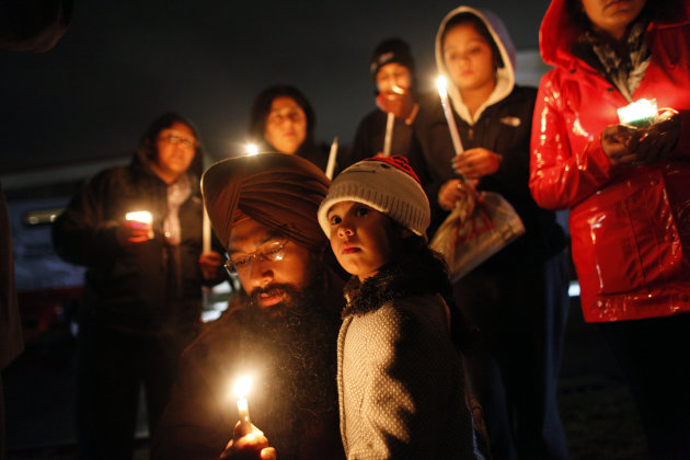 Eknoor Kaur, 3, stands with her father Guramril Singh during a candlelight vigil outside Newtown High School before an interfaith vigil with President Barack Obama, Sunday, Dec. 16, 2012, in Newtown,
