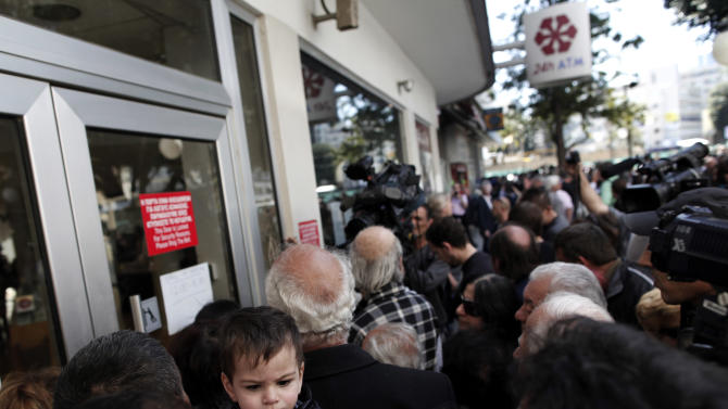People wait outside a branch of Laiki Bank in Nicosia, Thursday, March 28, 2013. Banks in Cyprus reopened to customers for the first time in nearly two weeks Thursday, albeit with strict restrictions on transactions, after being closed to prevent people withdrawing all their savings during the country's acute financial crisis. Large lines had formed outside the banks ahead of the opening of banks for six hours from noon. (AP Photo/Petros Giannakouris)