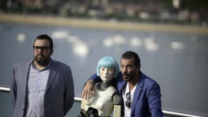 Spanish actor Banderas and director Ibanez pose next to a robot used in the film Automata during a photocall at the San Sebastian Film Festival