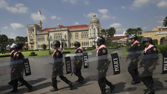 Thai policemen patrol inside the compound of Government House in Bangkok, Friday, Nov. 23, 2012. Anti-government protesters are expected to show up in Bangkok on Saturday to demand an overthrow of the current government under the rule of Prime Minister Yingluck Shinawatra. (AP Photo/Sakchai Lalit)