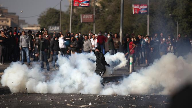 Egyptian protesters clash with riot police, unseen, near Tahrir Square, Cairo, Egypt, Tuesday, Jan. 29, 2013. Intense fighting for days around central Tahrir Square engulfed two landmark hotels and forced the U.S. Embassy to suspend public services on Tuesday. (AP Photo/Khalil Hamra)