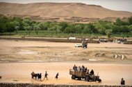 Afghan residents cross a river by tractor on the outside of Camp Phoenix where US soldiers are based near the town of Musa Qala in Helmand, Afghanistan on April 10, 2011. Eight civilians including seven women were killed in an insurgent roadside bombing in the southern Afghan province of Helmand on Wednesday, the interior ministry said