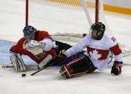 Canada's Billy Bridges (R) tries to score against Czech Republic's Michal Vapenka uring their ice sledge hockey game at the 2014 Sochi Paralympic Winter Games, March 11, 2014. REUTERS/Alexander Demianchuk (SPORT ICE HOCKEY OLYMPICS)