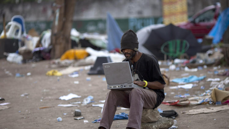 "In this photo taken Nov. 22, 2012, an alleged crack addict checks an out-of-commission laptop in Rio de Janeiro, Brazil. The South American country began experiencing a public health emergency in recent years as demand for crack boomed and open-air ""cracolandias,"" or crack lands, popped up in the sprawling urban centers of Rio and Sao Paulo, with hundreds of users gathering to smoke the drug. The federal government announced in early 2012 that more than $2 billion would be spent to fight the epidemic, with the money spent to train local health care workers, purchase thousands of hospital and shelter beds for emergency treatment, and create transitional centers for recovering users. (AP Photo/Felipe Dana)"