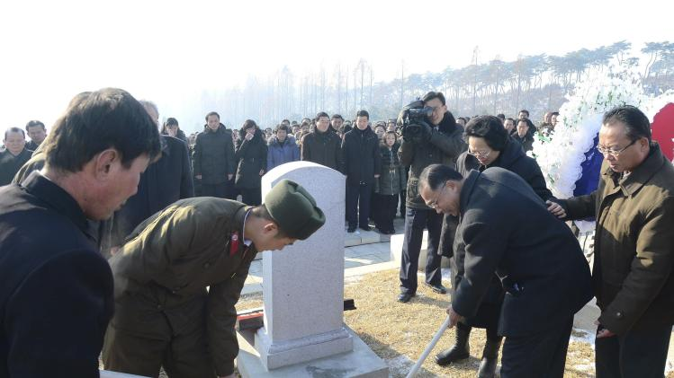 Attendees shovel earth into the grave of Kim Kuk Thae, chairman of the Control Commission of the ruling Workers' Party, during his state funeral