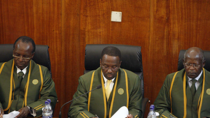 The six Supreme Court judges , led by Chief Justice Willy Mutunga, tcentre reads the verdict in the court in Nairobi Saturday, March 30, 2013. as Justice Jackson Ojwang, left, and Justice Philip Tunai, right. look on.  The Supereme Court on Saturday upheld the election of Uhuru Kenyatta as the country's next president ending the the election that riveted the nation amid fears of a repeat of the 2007-08 postelection violence. (AP Photo/Sayyid Azim)