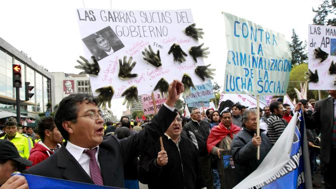 Demonstrators shout slogans as they hold a sign during a political rally against the government in Quito