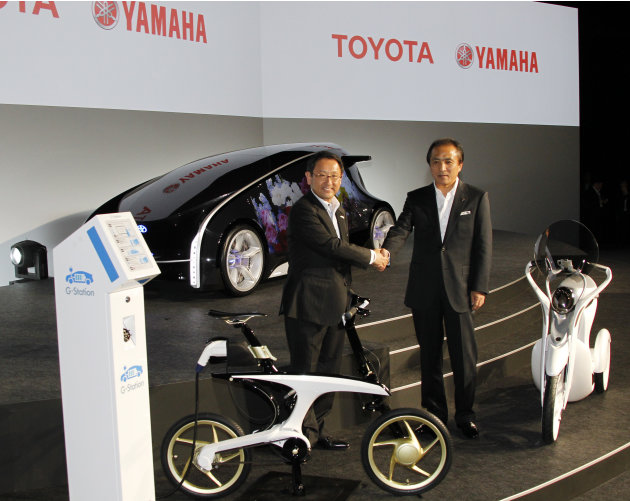 Toyota Motor Corp. President Akio Toyoda, left, shakes hands with Yamaha Motor Cor. President Hiroyuki Yanagi as they unveil next-generation vehicles, the electric commuter bike EC-Miu, right, and the