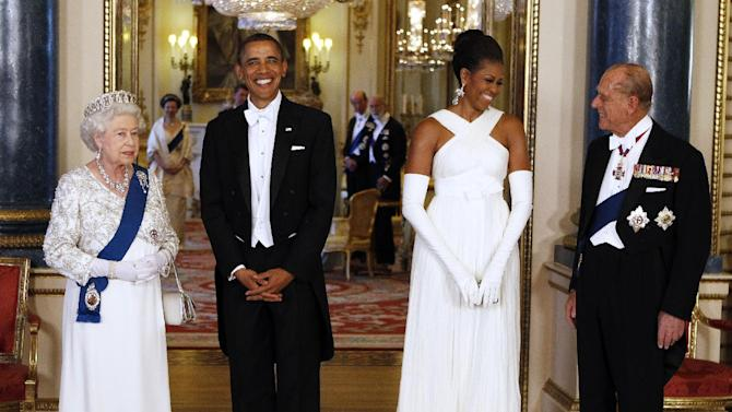 FILE - This May 24, 2011 file photo shows President Barack Obama, second left, and first lady Michelle Obama, with Queen Elizabeth II, left, and Prince Philip, right, prior to a dinner hosted by the queen at Buckingham Palace in London. Michelle Obama is wearing a white cross-neck halter gown by Tom Ford. Michelle Obama has proven her fashion savvy time and time again since she was introduced to the country as first lady on Inauguration Day 2009. In the past four years she has adeptly walked the line between directional fashionista and everywoman.  (AP Photo/Larry Downing, Pool)
