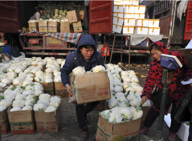 A Chinese man carries a box of cauliflowers at a farm produce wholesale market in Fuyang in central China's Anhui province Friday Jan. 11, 2013. China's inflation spiked to a six-month high in Decembe