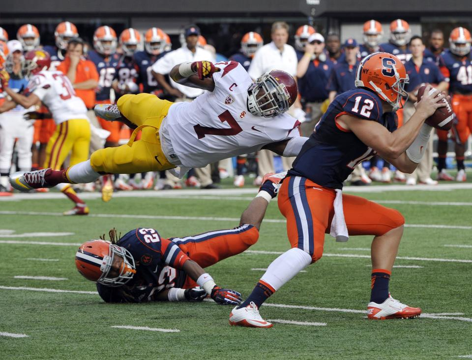 Syracuse quarterback Ryan Nassib, right, avoids a tackle by Southern California safety T.J. McDonald (7) as McDonald goes over Syracuse running back Prince-Tyson Gulley during the second quarter of an NCAA college football game Saturday, Sept. 8, 2012, in East Rutherford, N.J. (AP Photo/Bill Kostroun)