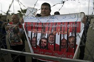 A man holds a poster behind barbed wire as riot policemen …