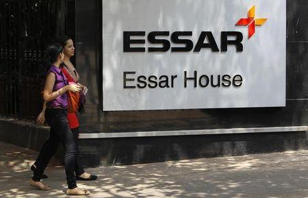 Employees walk past an Essar Group logo outside their headquarters in Mumbai
