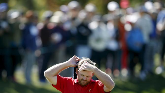 U.S. team member J.B. Holmes takes off his cap on the third green during the four ball matches of the 2015 Presidents Cup golf tournament in Incheon