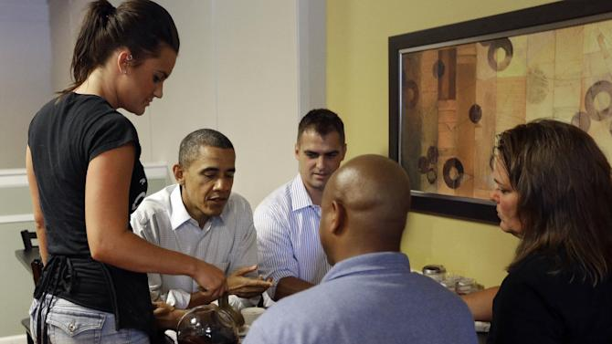 President Barack Obama sits down to have breakfast with local autoworkers, Daniel Schlieman, center, Heather Finfrock, far right, and James Fayson, center with back to camera, at Rick's City Diner, Monday, Sept. 3, 2012, in Toledo, Ohio. Serving coffee is waitress Megan Emch. (AP Photo/Pablo Martinez Monsivais)