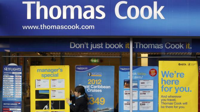 File photograph of a worker changing the window display of Thomas Cook in Loughborough