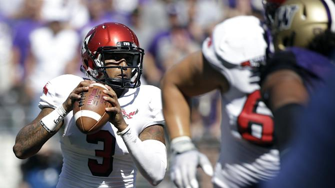 In this Sept. 6, 2014, file photo, Eastern Washington quarterback Vernon Adams Jr.,left, looks to throw against Washington during the second half of an NCAA football game in Seattle. Adams, one of the best players in FCS, is considering a transfer to Oregon, where he could replace Marcus Mariota next season. Graduate transfer quarterbacks often create a stir but while fans hope they're getting the next Russell Wilson there is no guarantee the next guy makes an impact