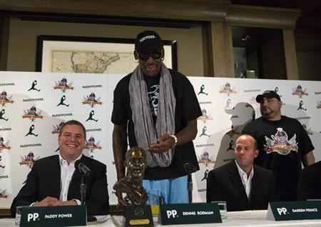 Former NBA basketball player Dennis Rodman (C) reacts to a bust of himself at a news conference in New York September 9, 2013.