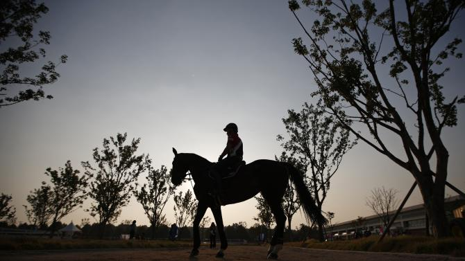 A competitor from Thailand is silhouetted during sunset during the equestrian Dressage Team competition at the Dream Park Equestrian Venue during the 17th Asian Games in Incheon