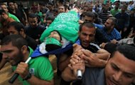 Palestinian mourners carry the body of Hamas militant Ismail al-Tili during his funeral in Beit Lahia, northern Gaza Strip, on October 24. The Israeli military said that Tuesday night&#39;s air strikes targeted rocket-launching squads who were about to fire on southern Israel