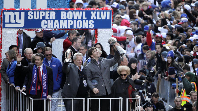 New York Giants' Eli Manning, second from right, holds up the Vince Lombardi trophy as a float makes its way up Broadway in New York, Tuesday, Feb. 7, 2012. Joining Manning are New York Gov. Andrew Cuomo, left, and Giants chairman Steve Tisch, center, holding the Halas Trophy. The Giants returned from their Super Bowl win to a celebration the likes that only New York can throw: a ticker-tape parade in the Canyon of Heroes on Broadway, where the city has honored stars for almost a century. (AP Photo/Seth Wenig)