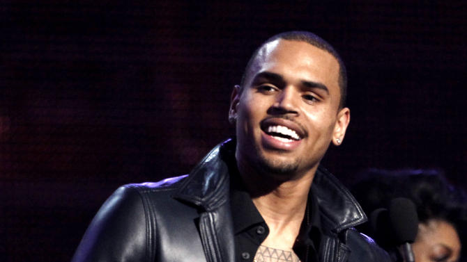 """FILE - In this Feb. 12, 2012 file photo, Chris Brown accepts the award for best R&B album for """"F.A.M.E."""" during the 54th annual Grammy Awards in Los Angeles. A judge in Los Angeles ordered a further review of Brown's community service on Monday, Sept. 24, 2012 and set another hearing to determine whether the singer is in compliance with the terms of his probation for the 2009 beating of then-girlfriend Rihanna. (AP Photo/Matt Sayles, File)"""