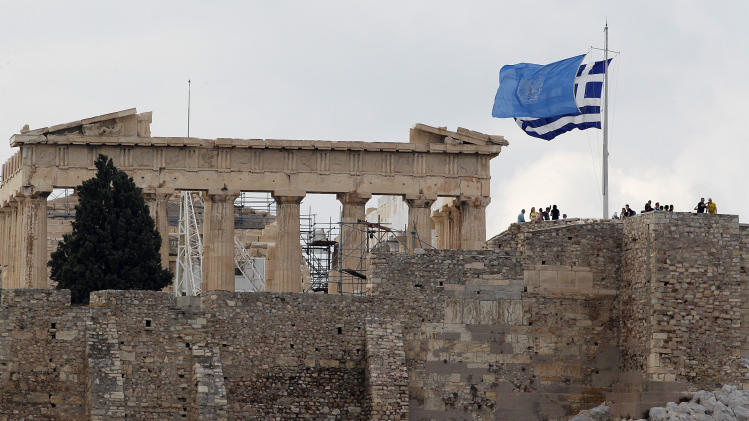 The UN flag waves next to the Greek one on top of Acropolis hill as the temple of Parthenon is seen in the background to mark the 67th United Nations Day in Athens on Wednesday, Oct. 24, 2012. (AP Photo/Dimitri Messinis)