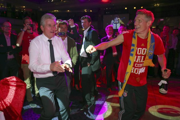 Bayern Munich's midfielder Bastian Schweinsteiger dances with coach Jupp Heynckes at the team's banquet in London
