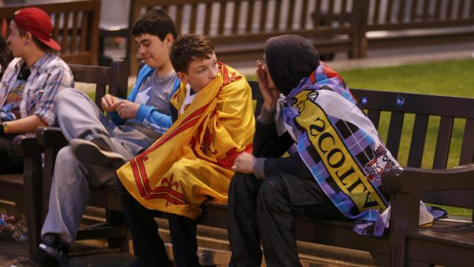 "Supporters from the ""Yes"" Campaign react as they sit in George Square in Glasgow, Scotland"