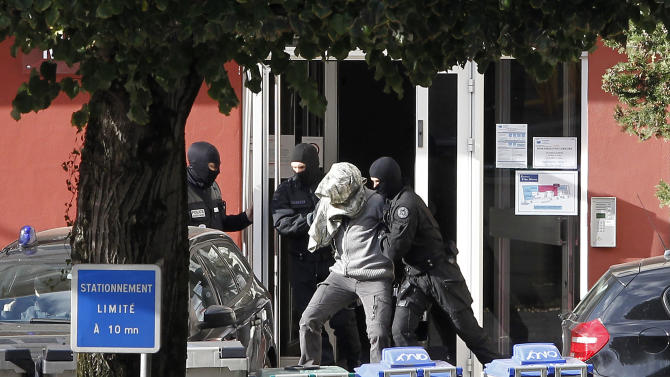 """A suspected member of ETA, surrounded by French Police officers, leaves the hotel where he was arrested with Izaskun Lesaka in the early hours of Sunday, in Macon, central eastern France, Sunday, Oct. 28, 2012. French police have arrested a top leader of the Basque separatist group ETA in eastern France, the Spanish interior ministry said in a statement on Sunday. Izaskun Lesaka, one of """"the three main leaders"""" of the banned organisation, was arrested during a raid by an elite French police unit at a hotel in the town of Macon, near the city of Lyon, it said. French police have arrested a top leader of the Basque separatist group ETA in eastern France, the Spanish interior ministry said in a statement on Sunday. Izaskun Lesaka, one of """"the three main leaders"""" of the banned organisation, was arrested during a raid by an elite French police unit at a hotel in the town of Macon, near the city of Lyon, it said.  (AP Photo/Laurent Cipriani)"""