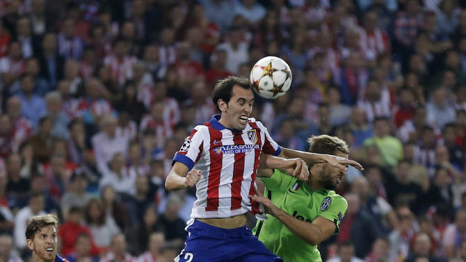 Atletico's Diego Godin, left, goes for a header with Juventus' Fernando Llorente during the Group A Champions League soccer match between Atletico De Madrid and Juventus at the Vicente Calderon stadium in Madrid, Spain, Wednesday, Oct. 1, 2014. (AP Photo/Daniel Ochoa de Olza)