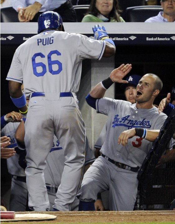 Los Angeles Dodgers' Yasiel Puig celebrates with Skip Schumaker after Puig hit a home run in New York