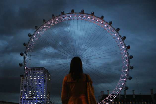 A woman watches as The EDF Energy London Eye is lit up on July 19, 2012 in London, England. The giant ferris wheel will be lit up with different coloured lights to reflect Tweets posted about the Lond