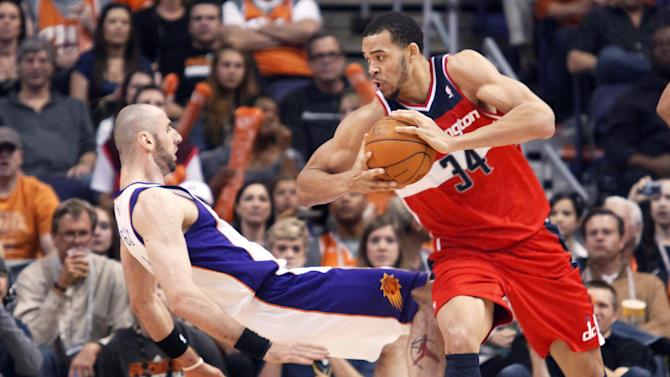 """FILE - In this Feb. 20, 2012, file photo, Phoenix Suns center Marcin Gortat, left, of Poland, falls backward to the floor as Washington Wizards center JaVale McGee, right, is called for a charge in the third quarter of an NBA basketball game in Phoenix. The NBA will penalize flopping this season, fining players for repeated violations of an act a league vice president says has """"no place in our game."""" The league said Wednesday, Oct. 3, 2012, that flopping will be defined as """"any physical act that appears to have been intended to cause the referees to call a foul on another player."""" (AP Photo/Paul Connors, File)"""