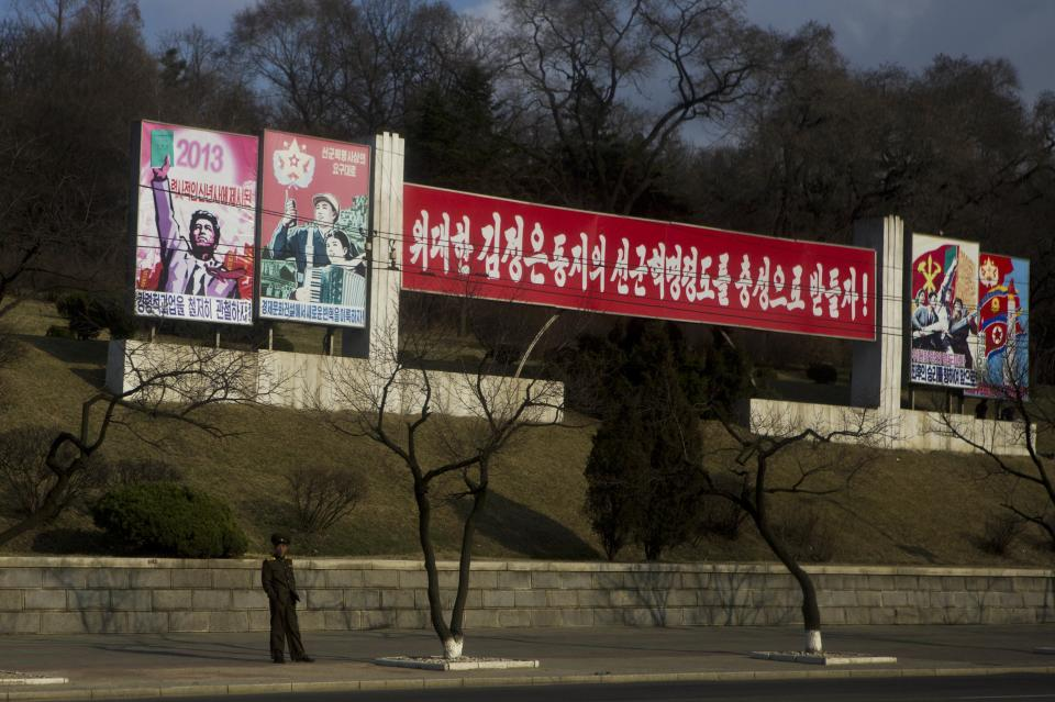 "A North Korean soldier stands beneath roadside propaganda which reads ""Let's Uphold the Military First Revolutionary Leadership of the Great Comrade Kim Jong Un With Loyalty"" in Pyongyang on Tuesday, April 9, 2013. (AP Photo/David Guttenfelder)"