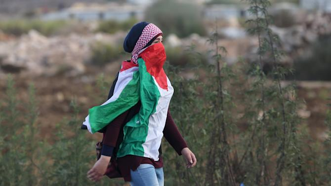 Masked Palestinian girl, draped in a Palestinian flag, walks during clashes with Israeli troops near the Jewish settlement of Bet El, near the West Bank city of Ramallah
