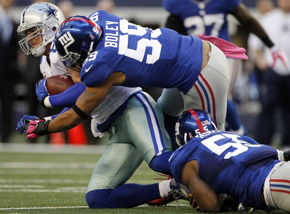 Dallas Cowboys tight end Jason Witten (82) is tackled by New York Giants outside linebacker Michael Boley (59) and Keith Rivers (55) during the first half of an NFL football game, Sunday, Oct. 28, 2012, in Arlington, Texas. (AP Photo/Tony Gutierrez)