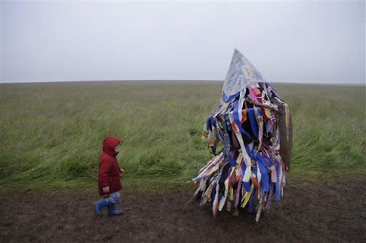 A man playing an accordion beneath a costume of torn fabrics and a child leave the Stonehenge monument in southern England, during the summer solstice after 04:52 am, Thursday, June 21, 2012. Beating drums latter-day druids and revelers flocked to Stonehenge through heavy rain to talk, dance and meditate as they waited for sunrise, which starts the longest day of the year in the northern hemisphere. Stonehenge, on the Salisbury Plain about 90 miles southwest of London, was built over three phases between 3,000 B.C. and 1,600 B.C. It is one of Britain's most popular tourist attractions; more than 750,000 people visit every year. (AP Photo/Lefteris Pitarakis)