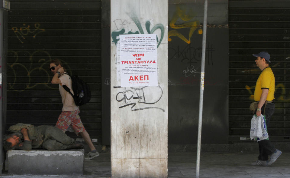 A homeless man sleeps on the ground as people pass by in central Athens, Saturday, June 16, 2012.  Greeks cast their ballots this Sunday for the second time in six weeks, after May 6 elections left no party with enough seats in Parliament to form a government and coalition talks collapsed.  (AP Photo/Petros Karadjias)