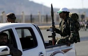 Houthi fighters ride a patrol truck in Sanaa