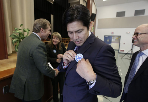 <p>               Sen. Kevin de Leon, D-Los Angeles, puts on a sticker for his proposed bill, SB39,  to fund energy efficiency projects at schools in California's poorest communities, before a news conference at Mark Twin Elementary School in Sacramento, Calif., Tuesday, Dec. 4, 2012.  The bill would use money from last month's voter approved initiative, Proposition 39, that requires  $500 million for five years be used for clean air project.(AP Photo/Rich Pedroncelli)